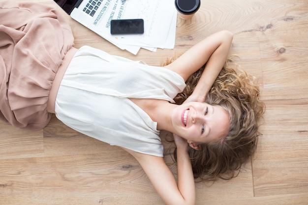 ハッピー美しい女の子は、床に横たわるとリラックス 無料写真