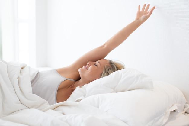 眠った後にベッドでストレッチする幸せな若い女性 無料写真