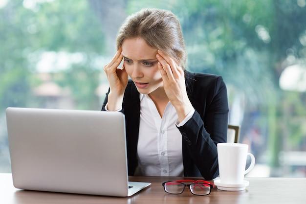 ノートパソコンを見て頭痛を持つ女性 無料写真
