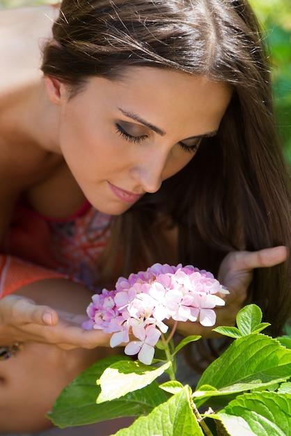 Молодая красивая девушка пахнет цветами, против зеленого летнего сада. Бесплатные Фотографии