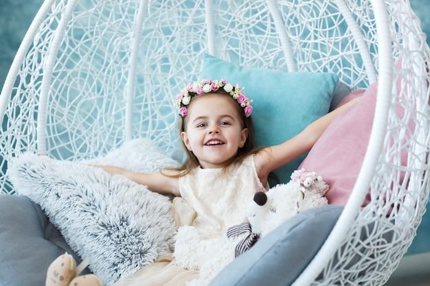 幸せな女の子は、白い掛かる椅子に座って、彼女の手を広げる 無料写真