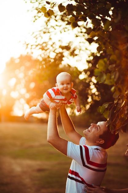 父は夕方の光の中に立って息子を抱きしめている 無料写真