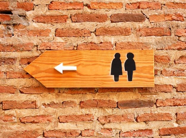 レンガの壁のトイレの標識と方向 無料写真