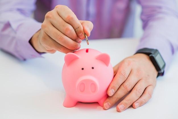 貯蓄と投資の概念の貯金箱のスロットにコインを置く男の手のビューを閉じます 無料写真