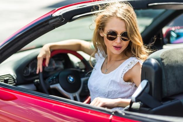 Секси девушка у красной машины