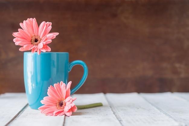 青マグカップ、装飾花と木の表面 無料写真