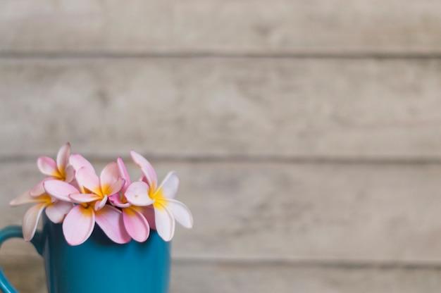 青マグカップや木製の背景に花のクローズアップ 無料写真