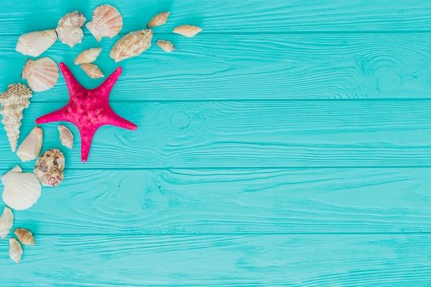 ヒトデ、貝殻、青い木製の表面 無料写真