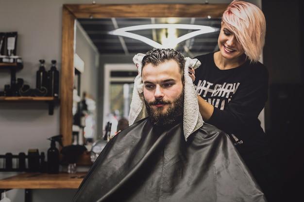 サロンで顧客の頭を拭く女性 無料写真