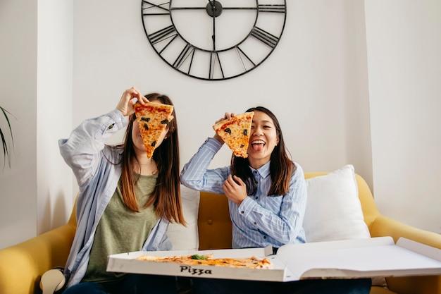 Довольно случайные девушки, с удовольствием наслаждаясь пиццей Бесплатные Фотографии