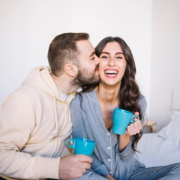 Пара с чашками, целующимися Бесплатные Фотографии
