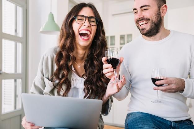 Смеющаяся пара с вином и ноутбуком Бесплатные Фотографии