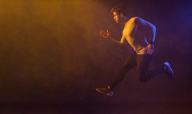 暗いスタジオでジャンプする運動男性 無料写真