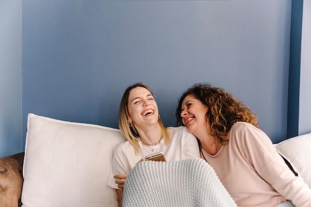 スマートフォンをブラウジングする女性を笑う 無料写真