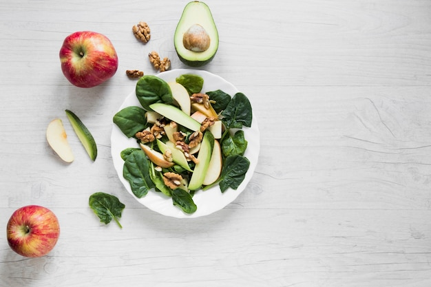 サラダの近くのリンゴとアボカド 無料写真