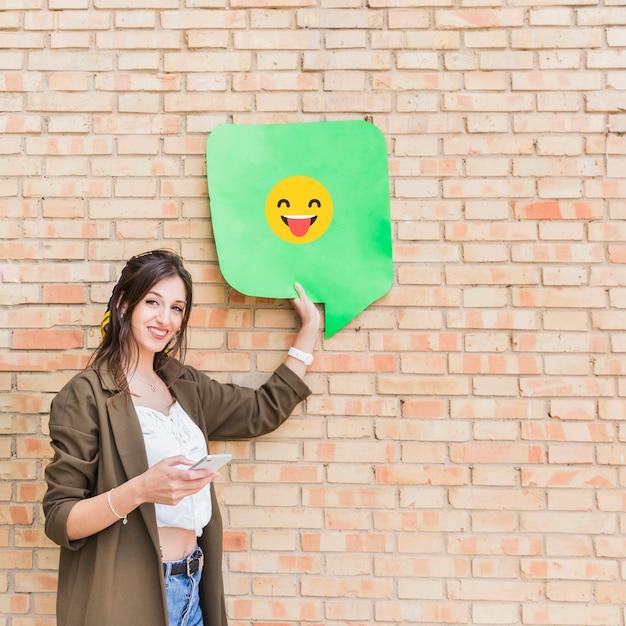 レンガの壁に携帯電話と幸せな絵文字メッセージを保持している魅力的な