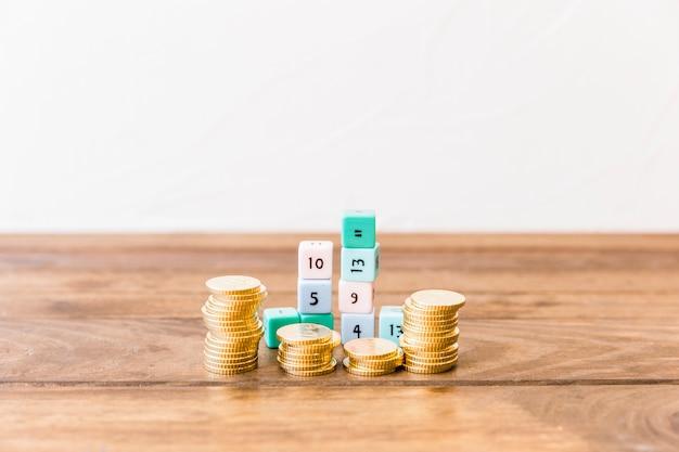 Сложенные монеты и математические блоки на деревянной столешнице Бесплатные Фотографии