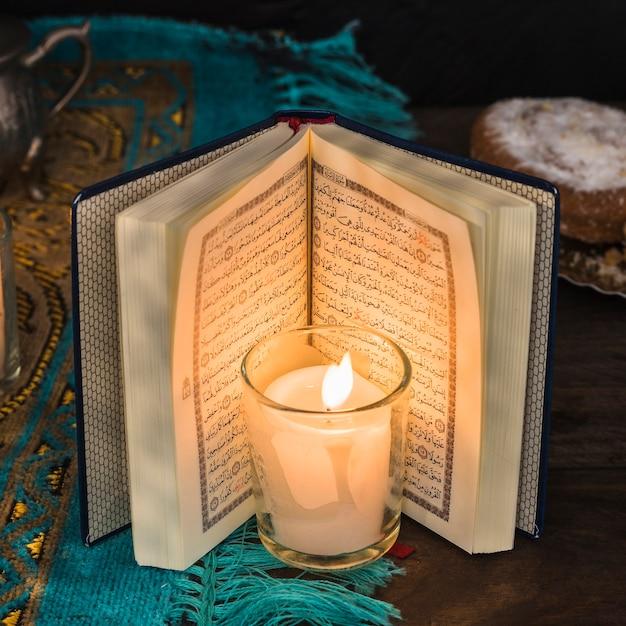 Крупный план горит свеча возле открытого корана фото | скачать.
