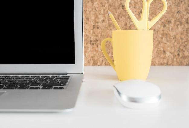 白い机の上に鉛筆を持つラップトップ、マウス、黄色のカップ 無料写真