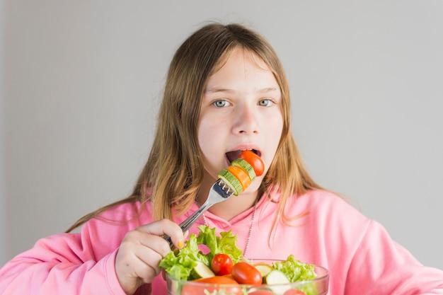 ガラスのボールで新鮮な健康な野菜サラダを食べる少女 無料写真