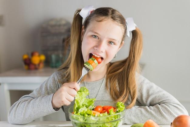 フォークと野菜サラダを食べる少女 無料写真