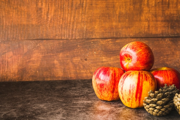 赤いリンゴと松のコーンの組成 無料写真