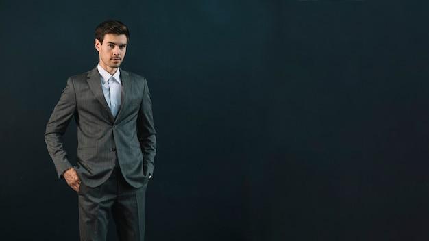 暗い背景に立っている若いビジネスマンの肖像 無料写真