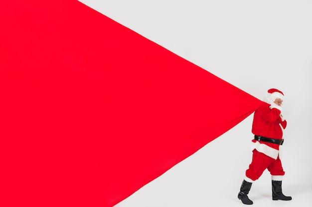 サンタクロースは巨大な袋を引っ張る 無料写真