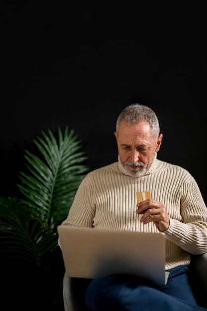 Пожилой мужчина с помощью кредитной карты, используя ноутбук Бесплатные Фотографии