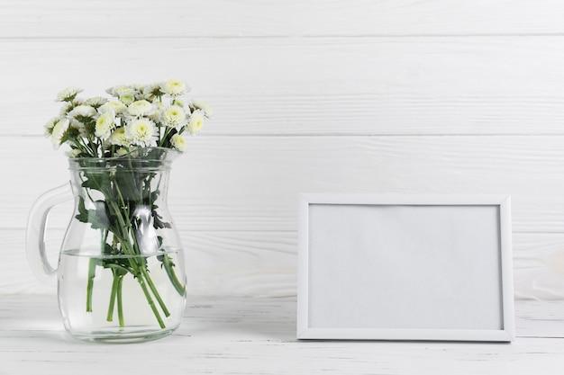 木製の背景の空白の枠に対してガラスの水差しの菊の花 無料写真
