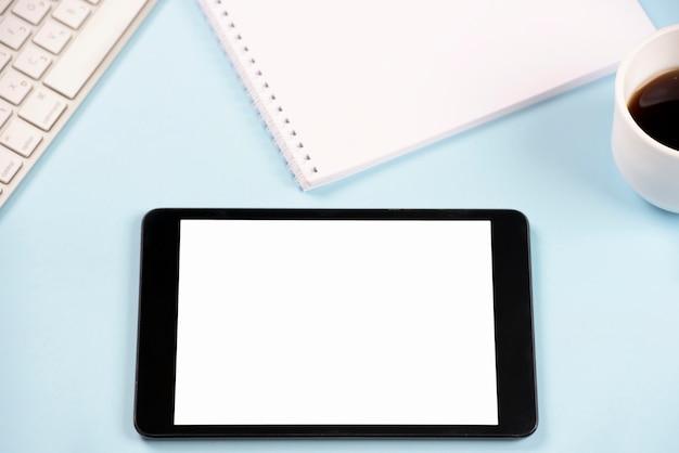 Цифровой планшет с клавиатурой; спиральный блокнот и чашка кофе на синем фоне Бесплатные Фотографии