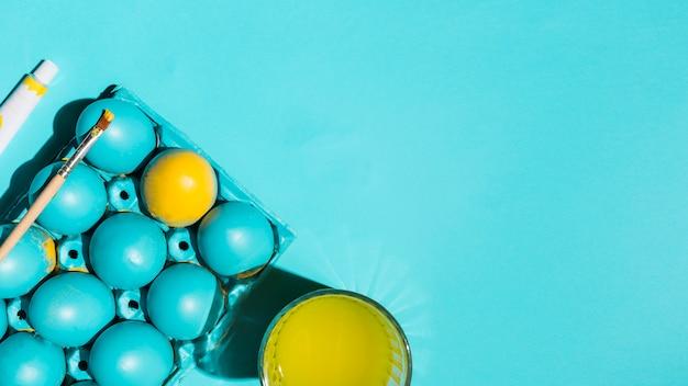 Пасхальные яйца в стойку с кистью и стакан воды на синем столе Бесплатные Фотографии