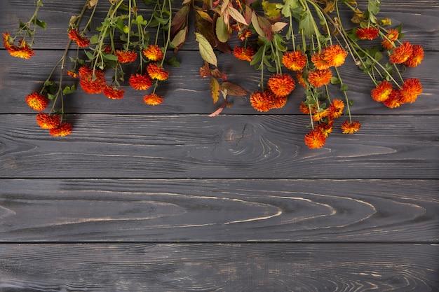 Красные цветы разбросаны по деревянному столу Бесплатные Фотографии