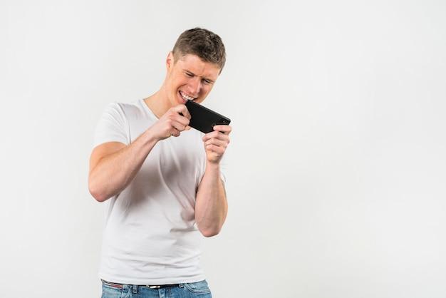 若い男が白い背景に対して携帯電話でビデオゲームをプレイ 無料写真