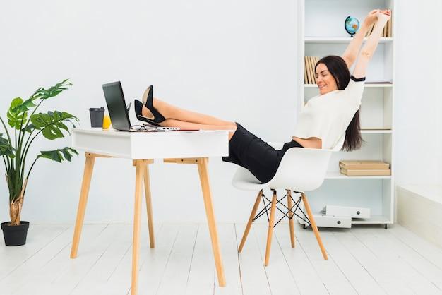 女性のオフィスのテーブルに座って腕を伸ばし 無料写真