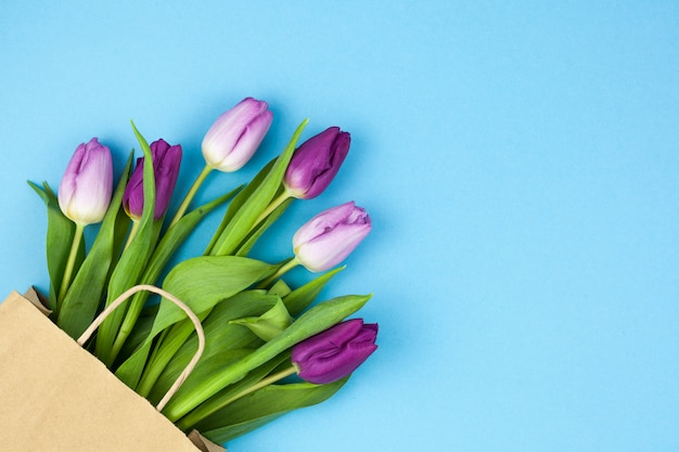 青い背景のコーナーに配置された茶色の紙袋と紫色のチューリップを束します。 無料写真