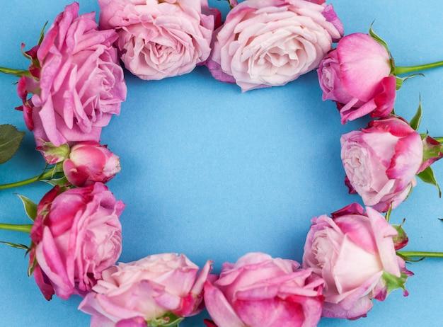 青い背景上のピンクのバラから作られた円形 無料写真