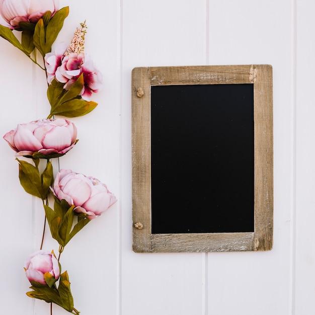 左の美しいバラとモックアップのためのスペースと黒板 無料写真
