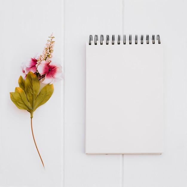 白い木の背景にバラをモックアップするためのノート 無料写真