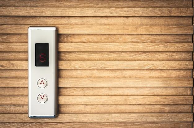 クローズアップエレベーターボタンとLedモニターの木の背景にコピースペース Premium写真
