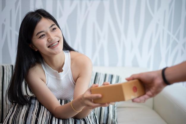 家で幸せに興奮した女性、彼女は贈り物の配達を受けています Premium写真
