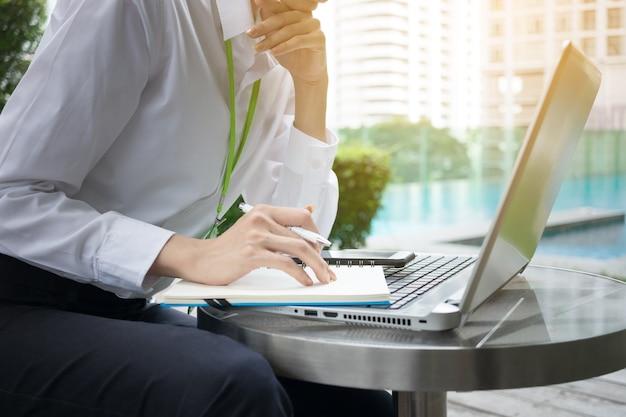 屋外でノートパソコンとノートブックで働くハッピービジネスの女性 Premium写真
