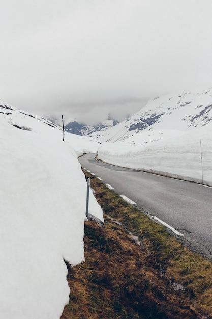 Дорога окружена большими глыбами снега Premium Фотографии