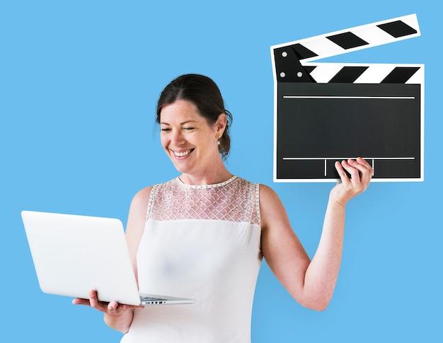 クラッパーとラップトップを保持している女性 無料写真