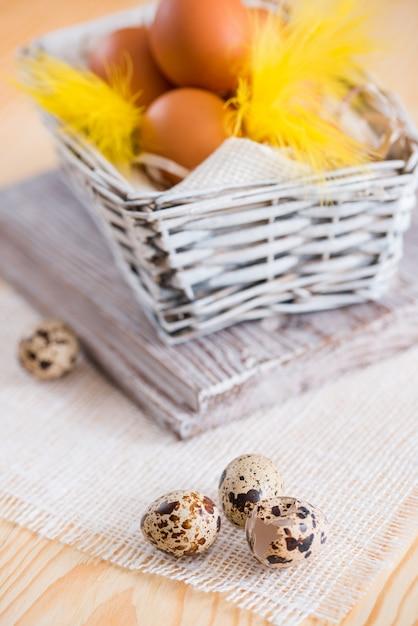 イースターフェザーフラットレイ。木製の背景にイースターエッグと黄色の羽 Premium写真