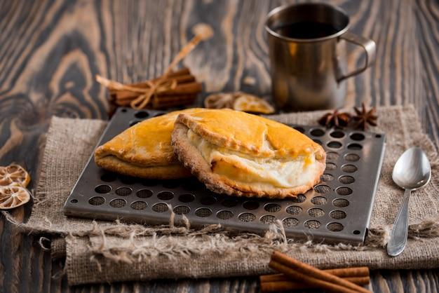 熱いお茶と木製のテーブルの上の甘いパンのカップ。上面図 Premium写真