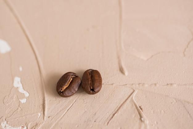 コンクリートブラウンピンクビンテージ背景に2つのコーヒーの穀物 Premium写真