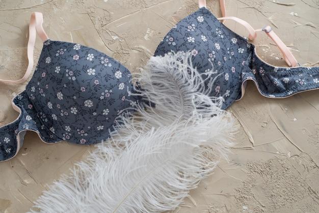 青いブラジャー、コンクリートの背景に分離されました。繊細な綿と白の羽毛 Premium写真