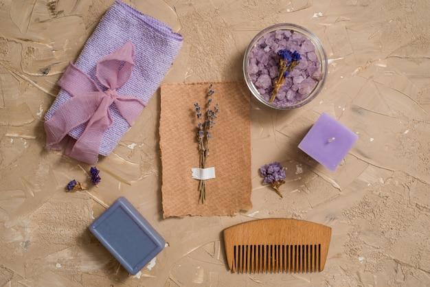 紫の海の塩、コンクリートの茶色の背景に木製の櫛タオル。 Premium写真