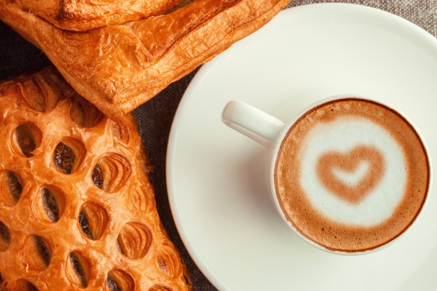 心とケーキとコーヒーのカップ。 Premium写真